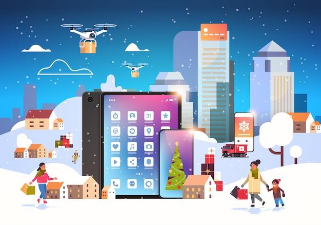 Люди с сумками гуляют на свежем воздухе с помощью мобильного онлайн-приложения готовятся к рождеству, новогодним праздникам, зимний городской пейзаж