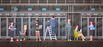 People Working In Data Center Room Hosting Server