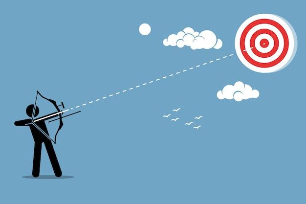 ターゲットに弓で矢を撃つ人。野心、使命、成功、および達成の概念。
