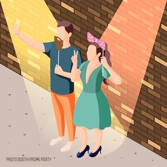 スポットライトで小道具を保持しているカップルと写真ブースパーティーお祝い等尺性レンガの壁