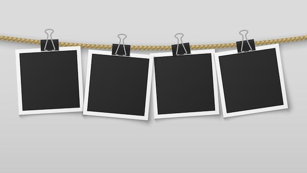 ロープにぶら下がっているフォトフレーム。空白のフォトペーパーフレーム、レトロな写真展と洗濯はさみ。画像きれい装飾縦壁カードアルバム