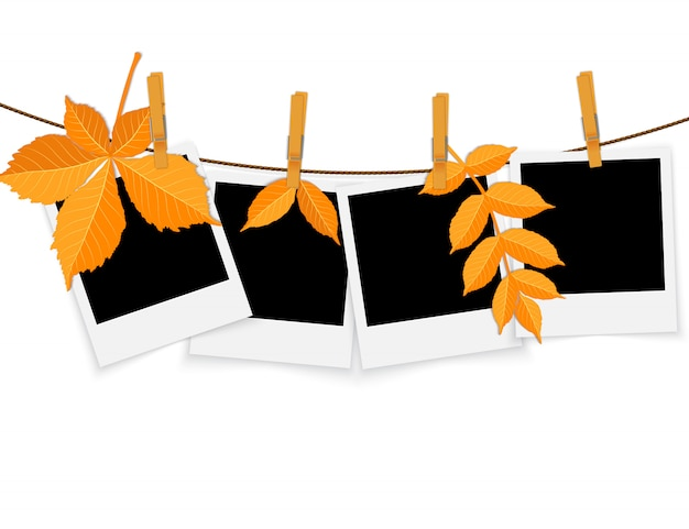 Photo frames on rope with clothespins and autumn leaves