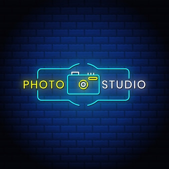 Photo studio neon signs style text design with camera icon in blue abstract bricks background.