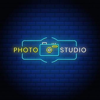 写真スタジオのネオンサインは、青い抽象的なレンガの背景にカメラアイコンとスタイルのテキストデザインです。
