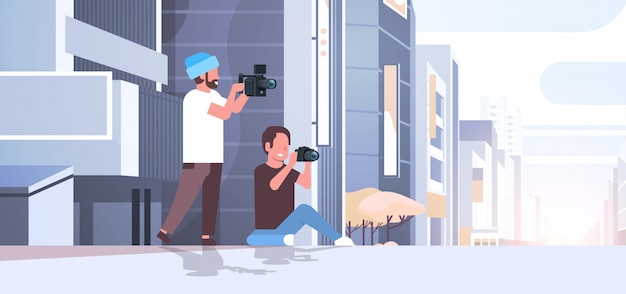 Photographer and cameraman using cameras shooting video taking pictures working together over modern city buildings exterior cityscape background horizontal full length flat