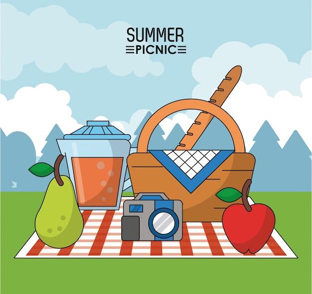 梨とジュース瓶とカメラとテーブルクロスのピクニックバスケット
