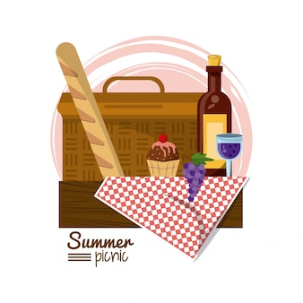 Picnic basket on tablecloth with bread dessert and wine