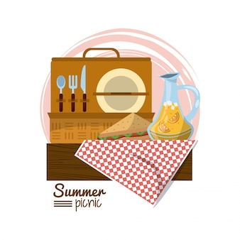 Picnic basket on tablecloth with sandwich and juice jar