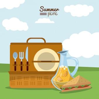 カトラリーセットとジュースジャーとサンドイッチを備えたピクニックバスケット