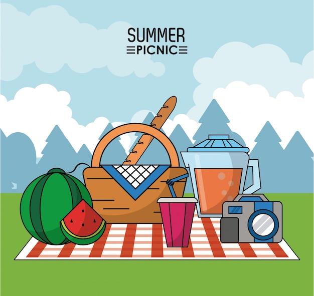 スイカとジュース瓶とカメラのテーブルクロスでのピクニック
