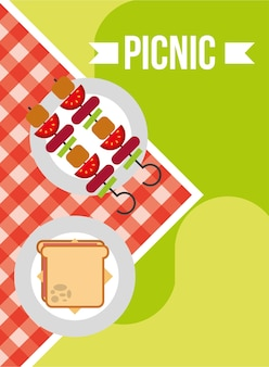 Picnic kebabs and sandwich on red checkred tablecloth