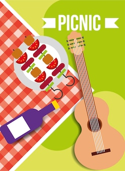 Picnic tablecloth wine bottle kebab and guitar