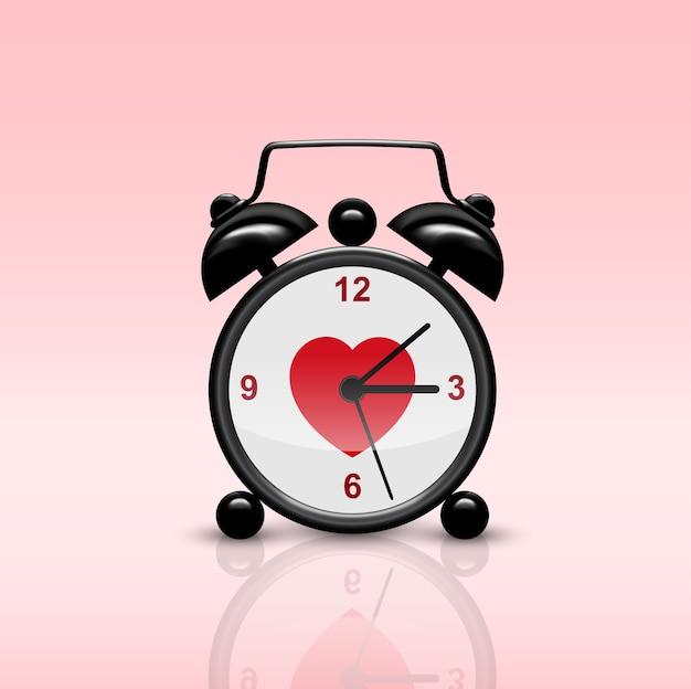 Изображение черного будильника на розовом фоне