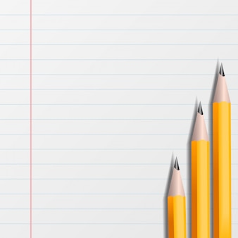 A piece of notebook in line with yellow pencils