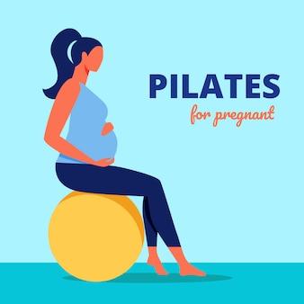 妊娠中のピラティス。体操のボールの上に座っている女性