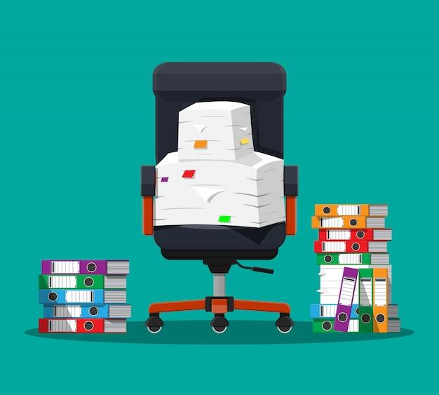 紙の書類やファイルフォルダーの山。