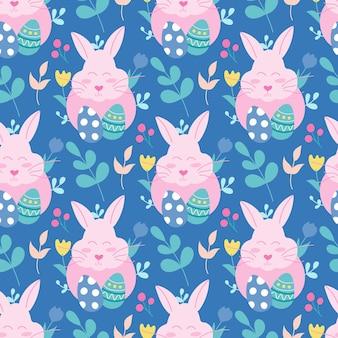 파란색 배경에 계란과 식물이 있는 분홍색 부활절 토끼. 벡터 완벽 한 패턴입니다.