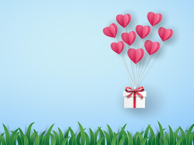 Pink origami hot air balloon in heart shape with gift box flying on the sky over the green meadow.