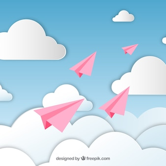 Pink paper planes in a cloudy sky