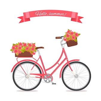 Pink retro bicycle with bouquet in floral basket and box on trunk.
