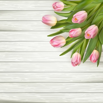 Pink tulips over white wood table, background