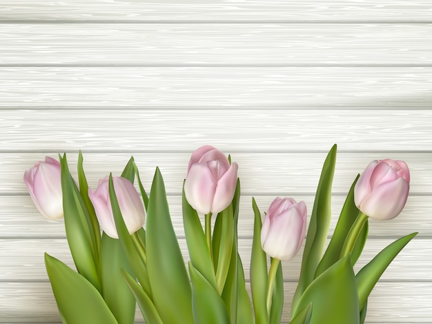 Pink tulips over white wood table.