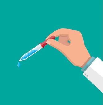 Пипетка с каплей в руках врача.