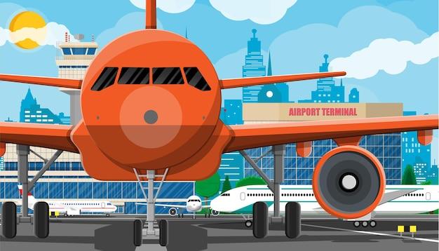 離陸前の飛行機。空港管制塔、ジェットウェイ、ターミナルビル、駐車場。都市の景観。雲と太陽と空。