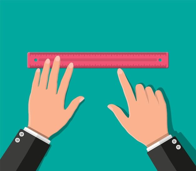 Пластиковая измерительная линейка в руке. инструменты для обучения и работы.