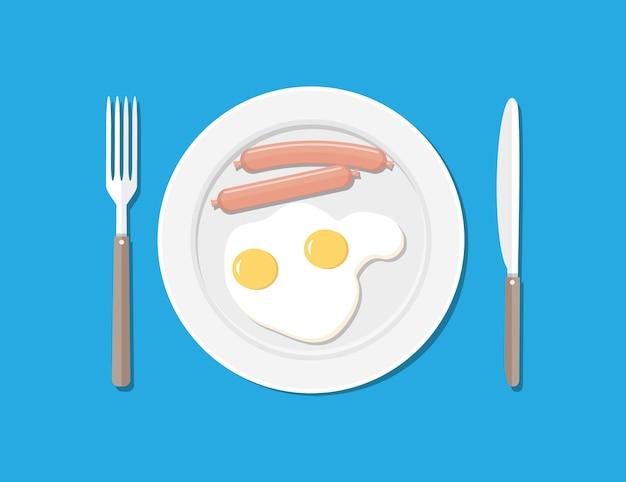 Тарелка, вилка и нож. яйца и колбасы