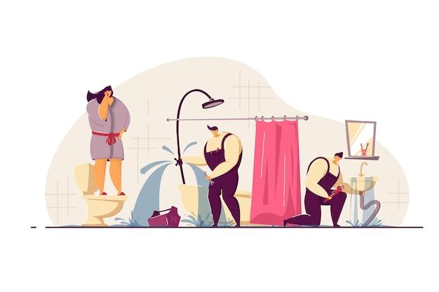Plumbers fixing leaky pipes in customers bathroom