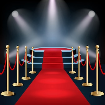 Podium with red carpet and barrier rope in glow of spotlights