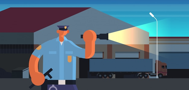 Police officer using flashlight policeman in uniform security authority justice law service concept night warehouse building exterior portrait
