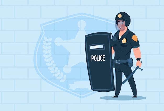 Policeman hold shield wearing helmet uniform cop guard over brick background