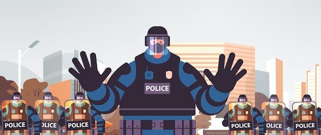 完全な戦術ギアの警官暴動警察官がジェスチャーの停止ジェスチャーを示し、デモが暴動マスコンセプト都市景観を制御