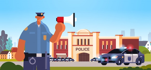 Policeman in uniform using loudspeaker making announcement security authority justice law service concept modern police station department building exterior portrait