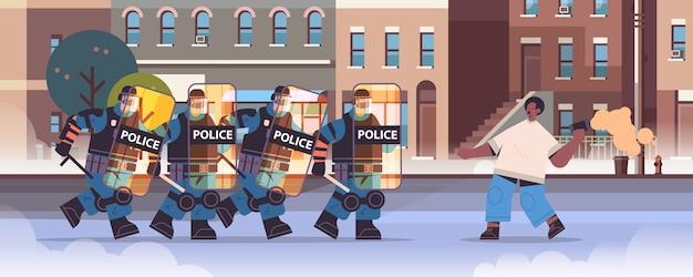 完全な戦術装備の警官が衝突デモの抗議の間に煙爆弾で抗議者を攻撃している暴動警察官