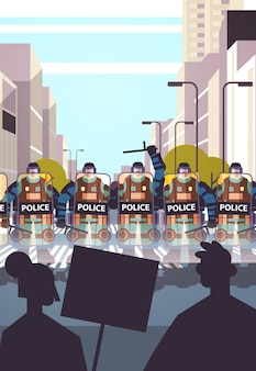 完全な戦術ギアの警官暴動デモ抗議暴動大衆概念都市景観垂直中にプラカードで通りの抗議者を制御する暴動警察官