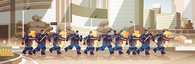 盾と警棒を持つ警官が抗議デモを一緒に立っている警察官を暴動コントロールコンセプト都市景観水平