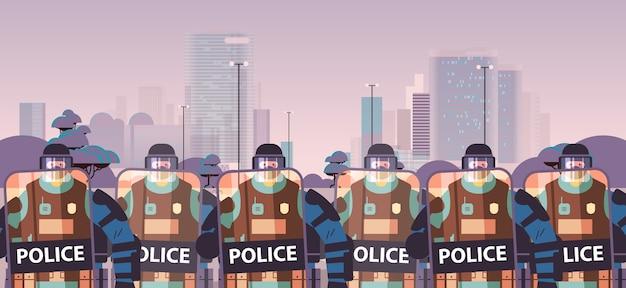 盾と警棒を持つ警官が抗議デモを一緒に立っている警察官を暴動制御コンセプトの街並み