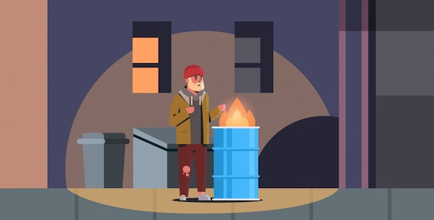 貧しいあごひげを生やした男が火で手を温めている乞食男がバレルのホームレスの無職ゴミで燃えるごみの近くに立っていることができる都市の夜の街