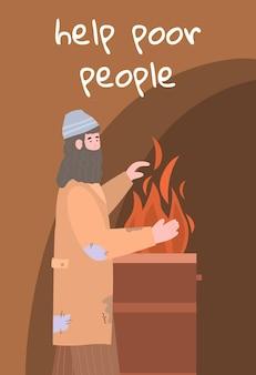 Бедный бездомный нищий в грязной рваной одежде греет руки возле бочки с огнем