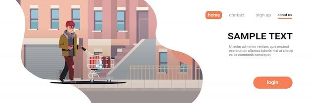 ホームレスの近代的な都市の建物の街並みの助けを懇願する通りの物乞いの男が通りを歩いてトロリーカートを押す貧しい男 Premiumベクター