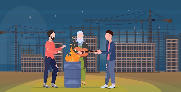Poor men group warming by fire beggars playing guitar standing near burning garbage in barrel homeless jobless unemployment concept construction site background horizontal flat full length