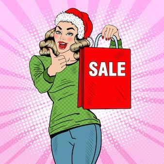 ポップアートクリスマスセールの買い物袋を持つ美しい女性は親指を立てます。図