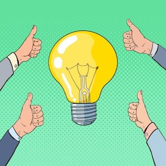 Поп-арт бизнес-идея с лампочкой и руками, показывая пальцы вверх.