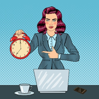 Pop art business woman holding alarm clock at office work with laptop.