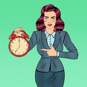 Поп-арт бизнес женщина держит будильник. время работать.