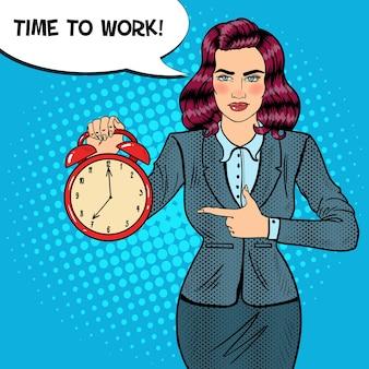 目覚まし時計を保持しているポップアートビジネス女性。働く時間。