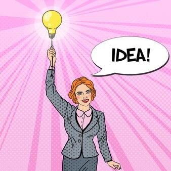 電球とポップアートビジネス女性。チームの仕事の概念。